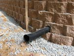 Drain pipe extending through retaining wall